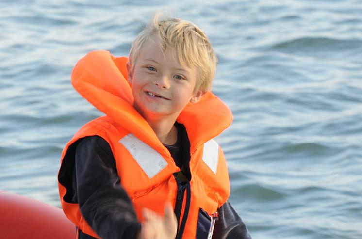 Sur une petite barque, navigant sur le bras de mer du Bélon, un jeune garçon en gilet de sauvetage et sa sœur nous sourient.