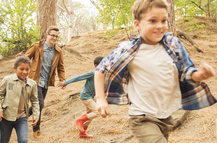 Ungroupe de 7 enfants courent dans la forêt, sur un chemin de terre, accompagnés de 2 animateurs. En arrière plan, un monticule entouré d'arbres.