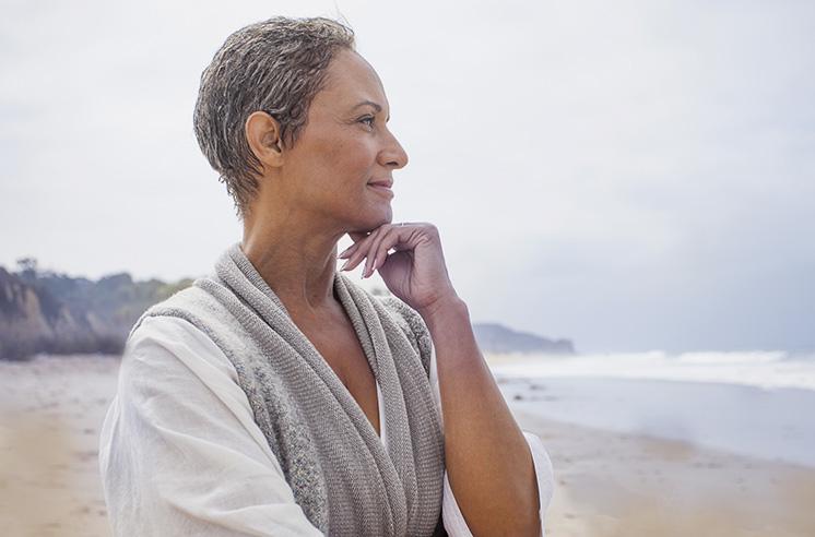 Au premier plan, une femme d'une cinquantaine d'années sur une plage, sourit, pensive, en regardant vers l'horizon. Au second plan, on aperçoit des falaises.