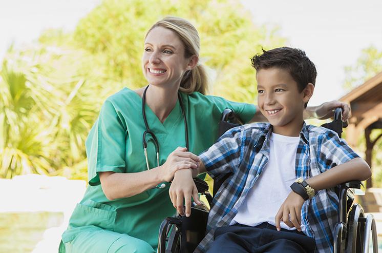 Un enfant en fauteuil roulant et son accompagnante, en tenue d'infirmière, regardent au loin. Ils ont l'air joyeux. Derrière eux, des arbres et une construction en bois dont on aperçoit le toit.