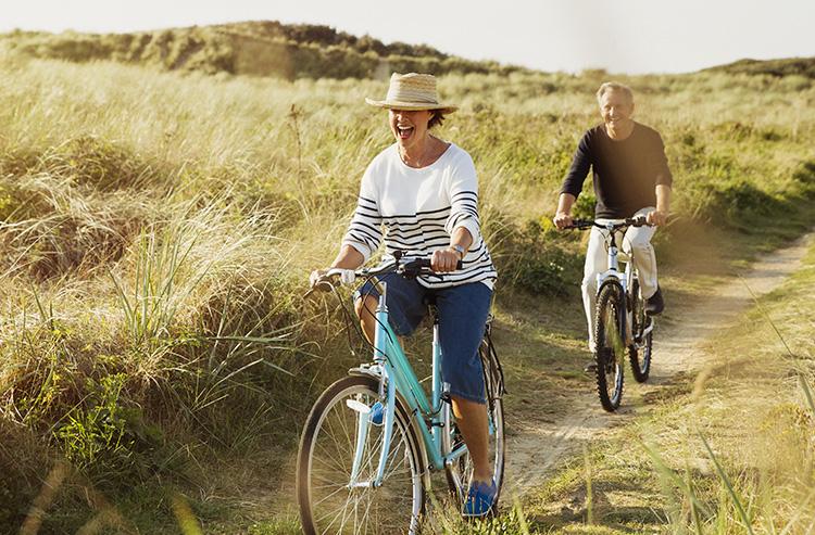 Un couple, dont la femme est en marinière, se balade en vélo dans la campagne. Les herbes sur le coté du chemin cyclable sont hautes et verdoyantes.