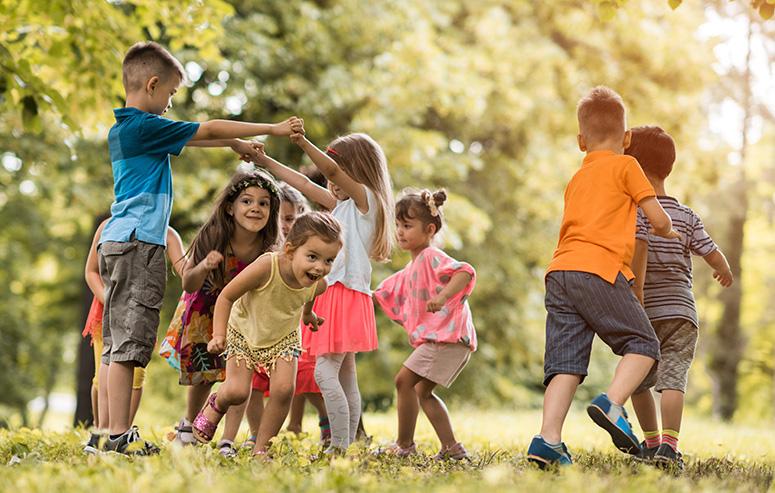 Un groupe de 8 enfants jouent dans la forêt sous le soleil breton. Ils sont joyeux.