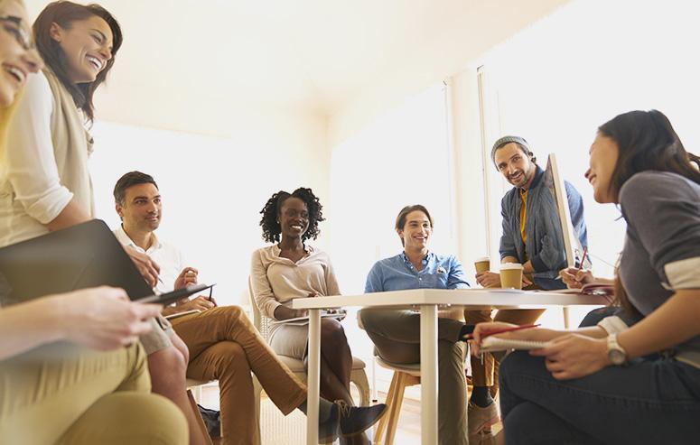 Plan en contre plongée d'un groupe de 8 personnes en réunion dans une salle. Ils sont assis autour d'une table et écoutent en souriant une femme en train de parler.