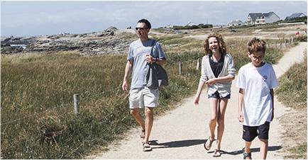 Une famille, deux parents et leur enfant, se dirigent vers la plage. Le père en lunettes de soleil regardent vers l'horizon, le jeune adolescent marche en regardant le sol, la mère rit aux éclats. En arrière plan, des maisons blanches et leurs toiturs grises.