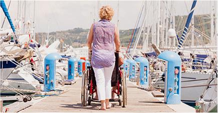 Une femme de dos marche sur un ponton entouré de bateaux. Elle pousse une personne en fauteuil roulant.