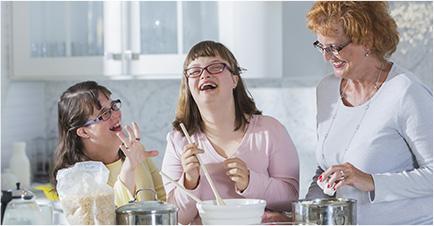 3 femmes (2 adolescentes et une adulte) rient aux éclats en préparant une recette de gâteau dans une cuisine.