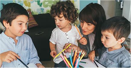 3 enfants dessinent autour d'une table ronde. Une jeune femme, agenouillée pour être à leur hauteur, leur parle.