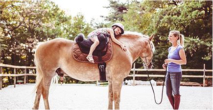 Une petite fille, heureuse, assise sur un cheval, enlace l'animal. La professeur d'équitation tient les cordes et la regarde en souriant.