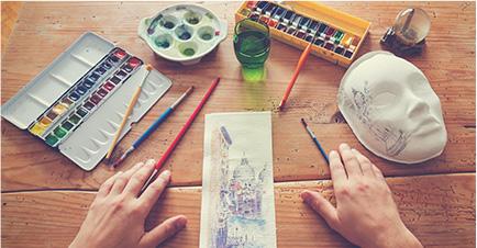 Il s'agit d'une photo en gros plan des mains d'une personne posées sur une table en bois. Des tubes de peintures aquarelle et d'encre, des pinceaux, une feuille et un masque sont disposés autour.