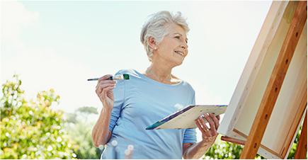 Gros plan d'une femme d'environ 70 ans qui peint un tableau dans son jardin. Elle sourit en regardant sa création.