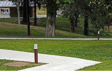 Parc du domaineavec des chemins qui parcourent en zigzag la pelouse taillée du camping.