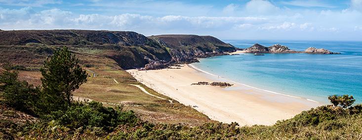 Au premier plan une colline qui surplombe une plage. Plus loin, le banc de sable blanc et la mer calme couleur bleu azur.